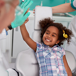 young girl giving dentist high five