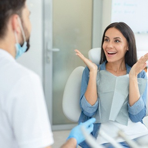 A woman happy with her smile while talking to her dentist