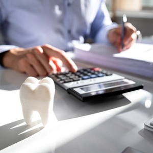 A person using a calculator with a model of a tooth on a desk