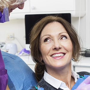 older woman smiling up at dentist