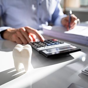 Man calculating cost of care with tooth on desk