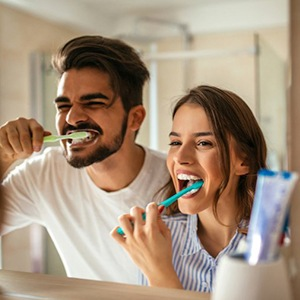 A couple brushing their teeth together