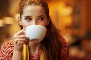A woman drinking out of a mug.