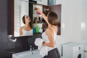 woman cleaning out medicine cabinet