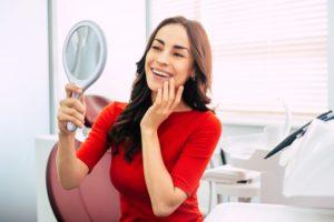 Woman admiring smile after receiving dental implants in Jacksonville