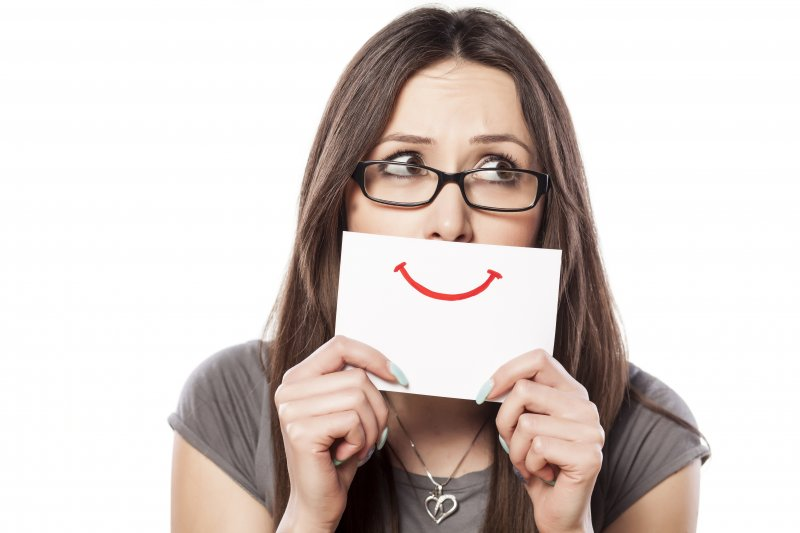 a woman wearing glasses holds up a white card with a red smile attempting to hide her crooked teeth