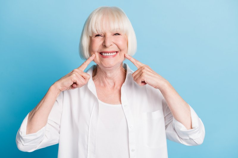 An older woman points to her new dentures in Jacksonville
